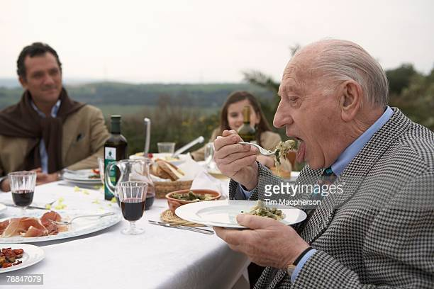 Three generation family eating outdoors
