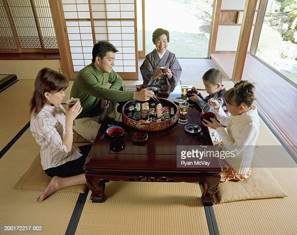 Three generation family eating sushi, elevated view