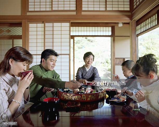 3 つの世代の家族の寿司を食べる