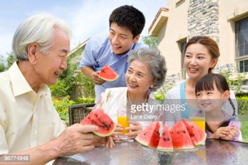 Three generation family eating watermelon