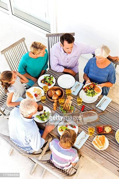 3 つの世代の家族がお料理をテーブルにポーチ