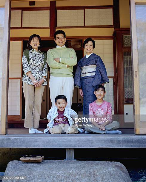 Three generation family in open doorway, smiling, portrait