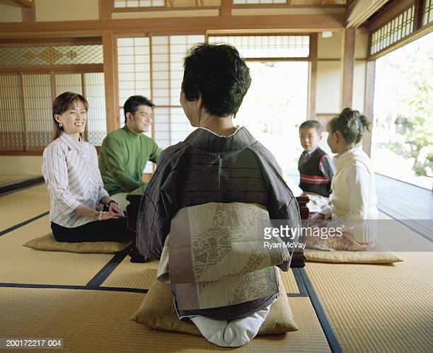 Three generation family kneeling on cushions at table, talking