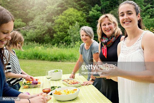 Three generation family of women preparing food outdoors. : Stock Photo