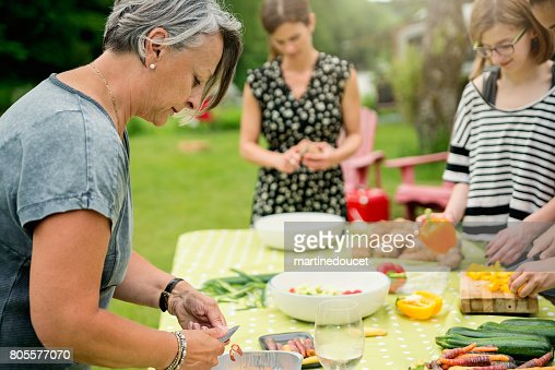 Three generation family of women preparing food outdoors. : Stock Photo