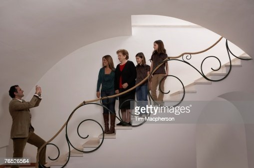 Three generation family on staircase posing for photograph