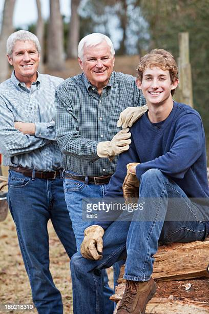 Three generation family outdoors by woodpile