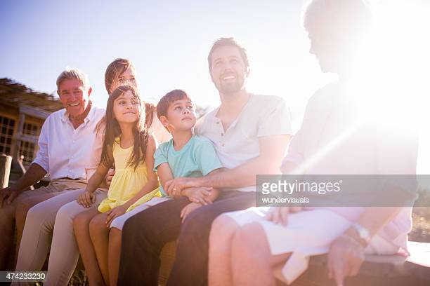 Three generation family outdoors together with sun flare