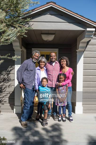 Three generation family outside house