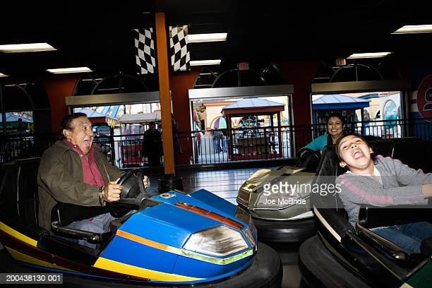 Three generation family riding bumper car at amusement park