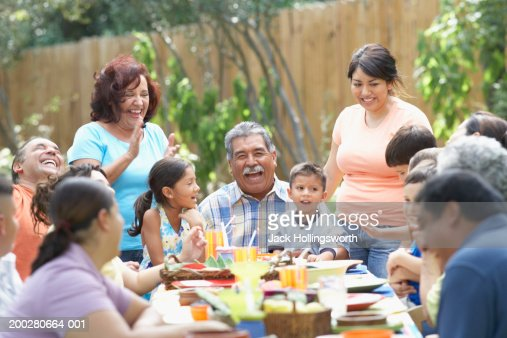 Three generation family sitting at a picnic table : Stock Photo