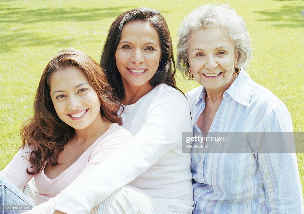 Three generation family sitting on lawn, portrait : Stock Photo