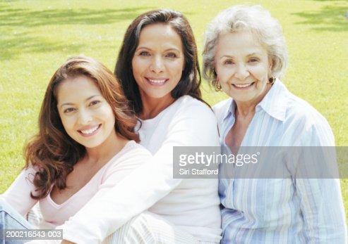 Three generation family sitting on lawn, portrait : Stock Photo