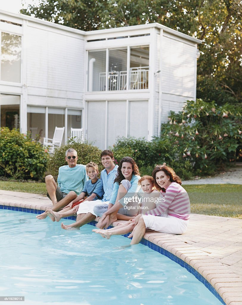 Three Generation Family Sitting Poolside In A Garden Stock