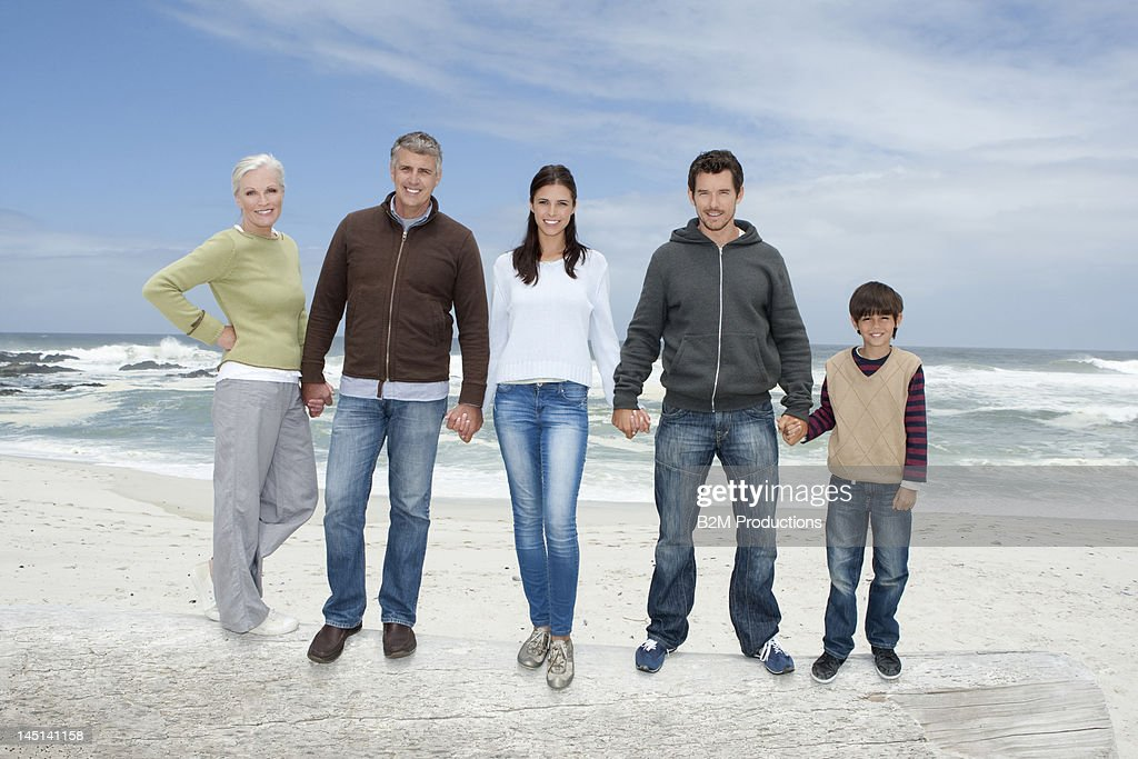 Three generation family standing on driftwood : Stock Photo