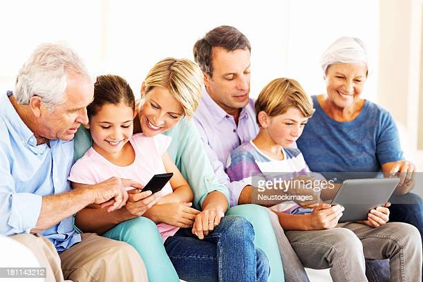 Three Generation Family Using Smart Phone And Digital Tablet