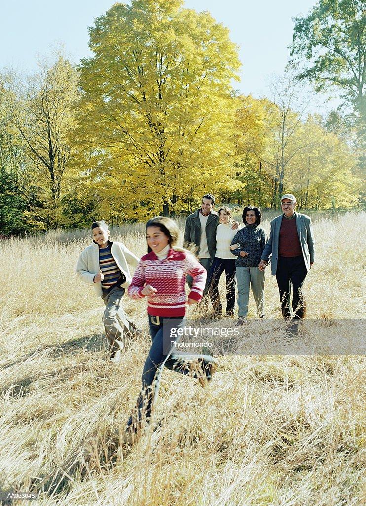Three generation family walking across field : Stock Photo