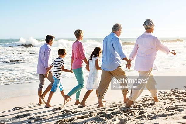 Trois générations de la famille marche en tenant les mains sur la plage