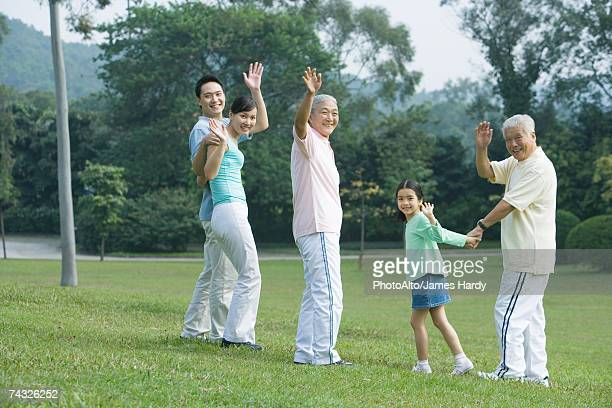 Three generation family waving at camera