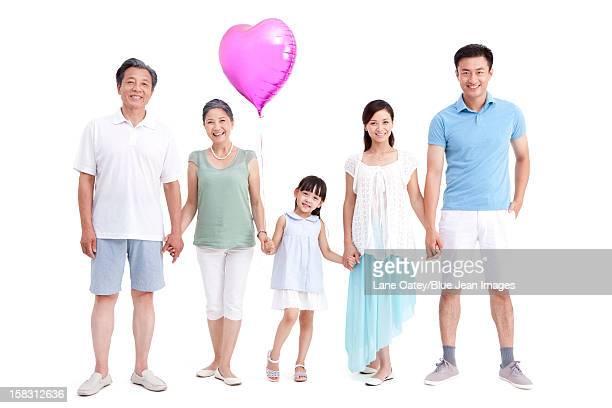 Three generation family with a heart-shaped balloon