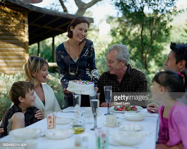 Three generation family with two children (6-7, 8-9) celebrating birthday in garden