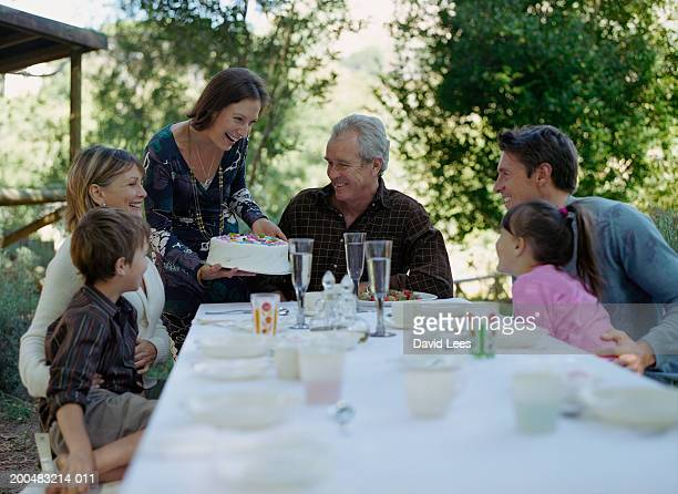 Three generation family with two children (6-7, 8-9) celebrating birthday in garden