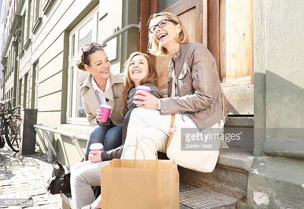 Three generation females drinking takeaway coffee on street