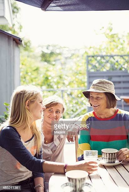 Three generation females having coffee in yard