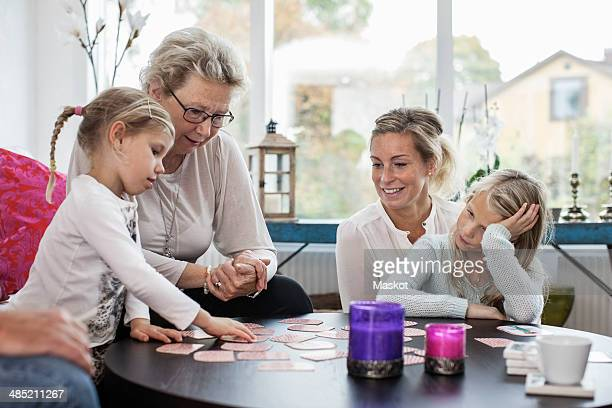 Three generation females playing card puzzle game at home