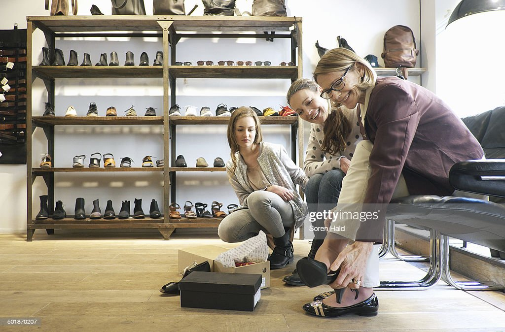 Three generation females trying out shoes in shoe shop