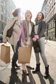 Three generation females with shopping bags on city street