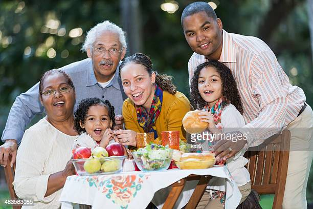 Three generation Hispanic family at picnic table