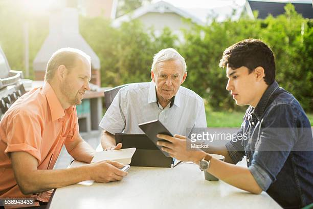 Three generation males using technologies at table in yard