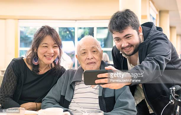 Three Generation, Multi-Ethnic Asian, Eurasian Family Taking Selfie with Smartphone
