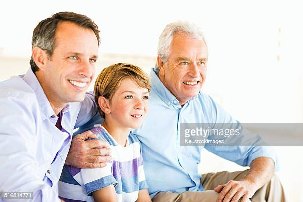 Three Generation Of Males Looking Away While Sitting At Home