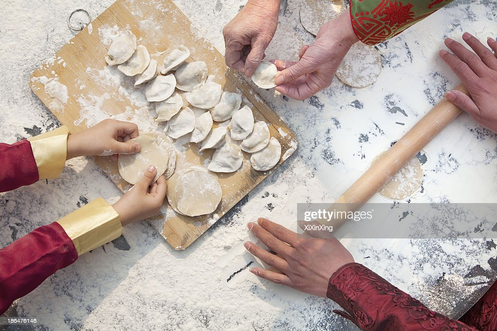 Three generation of women making dumplings, hands only : Stock Photo
