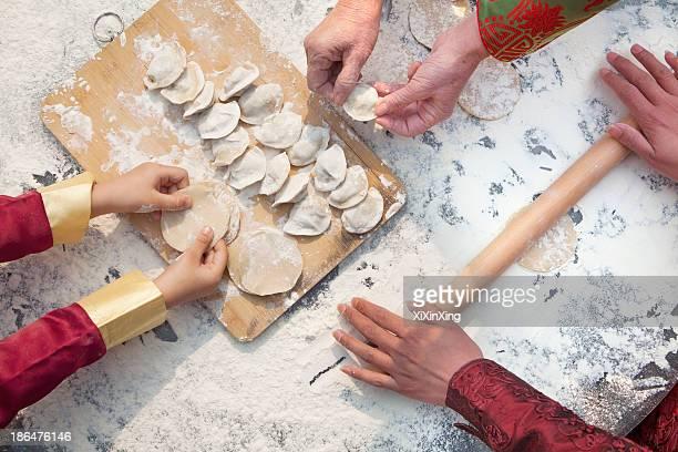 Three generation of women making dumplings, hands only