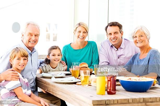 Tres generacional familia tener comida en la mesa en el Patio