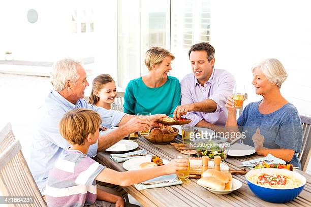 Three Generational Family Having Meal Together Al Fresco