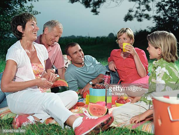 Three generational family picnicing in countryside, sitting on blanket