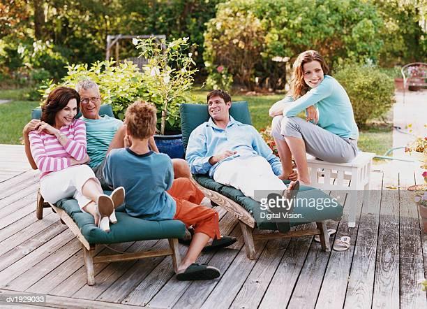 Three Generational Family Sit on Decking in Their Garden