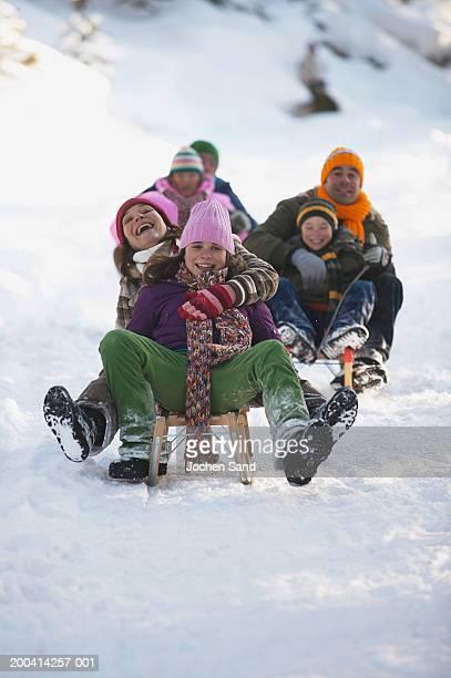 Three generational family tobogganing in snow, smiling