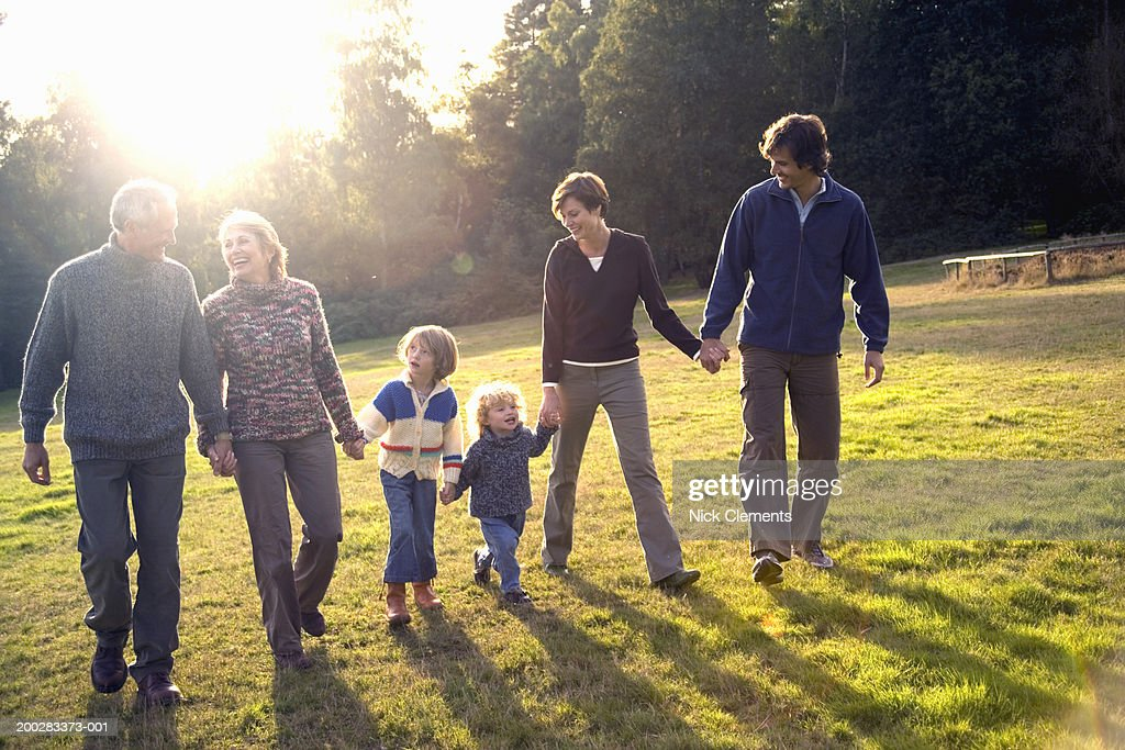 Three generational family walking hand in hand in park, smiling : Stock Photo