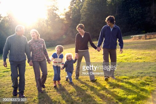 Three generational family walking hand in hand in park, smiling : Photo
