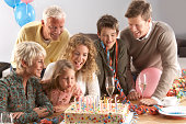 Three generational family with children (5-10 years), granddaughter blowing out candles on birthday cake