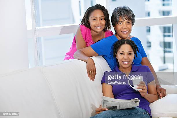 Three generational females sitting on couch smiling at camera