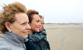 Closeup of three generations female looking at sea on the beach in autumn. Background focus on young woman and child