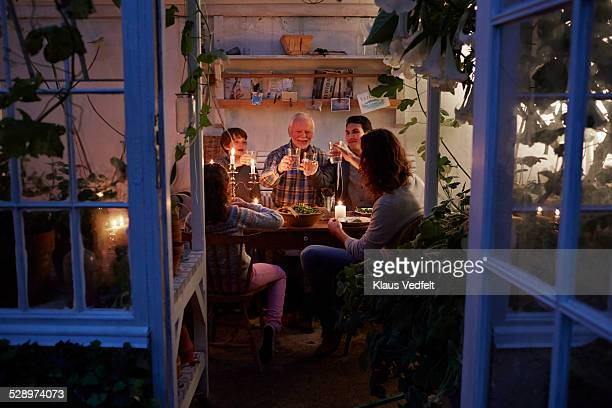 Three generations having cozy meal in garden house