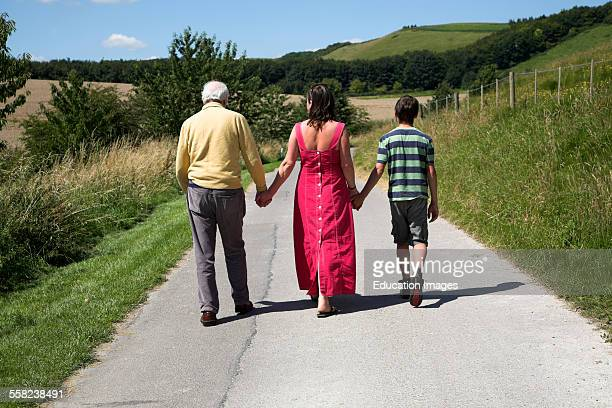 Three generations of a family holding hands walk into the future along a country lane viewed from behind
