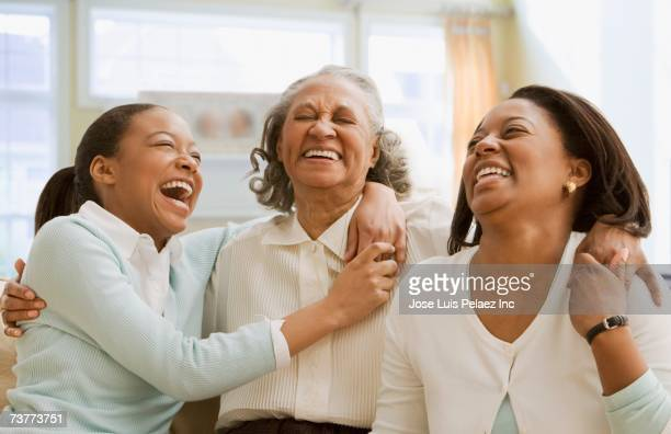 Three generations of African women laughing